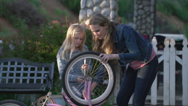 MS Mother teaching her daughter how to fix her bike