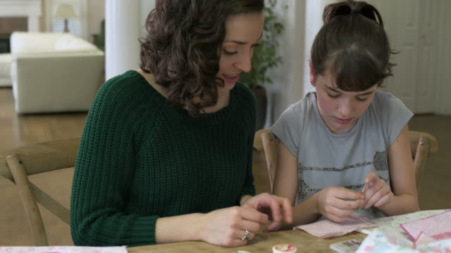 Mother teaching her daughter how to sew