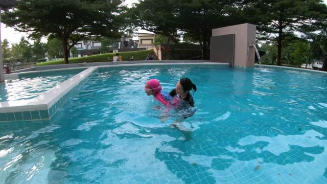 mor undervisning hennes dotter hur man simma i poolen - utebassäng bildbanksvideor och videomaterial från bakom kulisserna