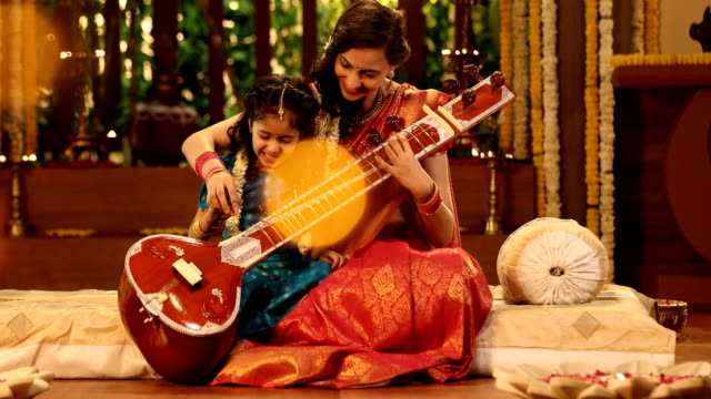 ms mother teaching her daughter to play sitar during pongal festival / new delhi, india - daughter stock videos & royalty-free footage