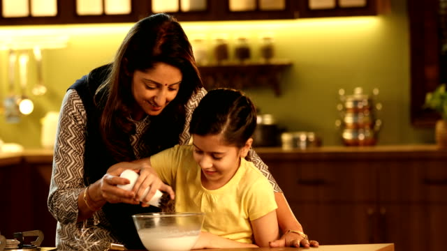 ms mother teaching her daughter to prepare food in kitchen / delhi, india - 腕をまわす点の映像素材/bロール