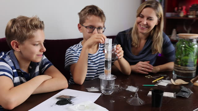 mother teaching kids about water purification and filtration - diy stock videos & royalty-free footage