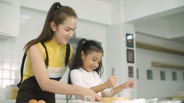 mother teaching little daughter how to make a dough for cookies or a cake in kitchen - daughter stock videos & royalty-free footage