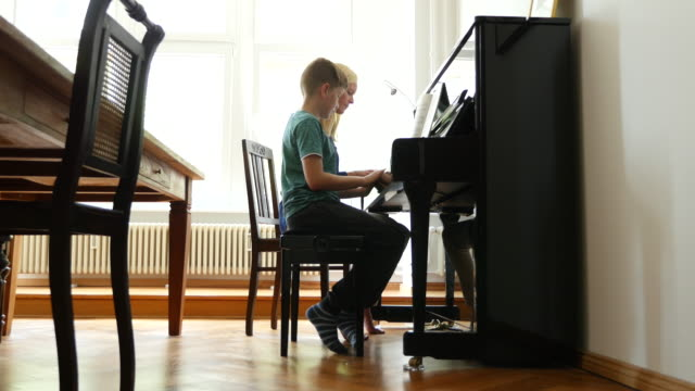 mother teaching piano to son while sitting at home - piano stock videos and b-roll footage