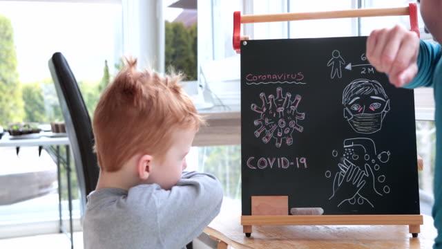 vídeos y material grabado en eventos de stock de madre enseñando hijo pelirrojo sobre coronavirus y cóvidio-19 - son