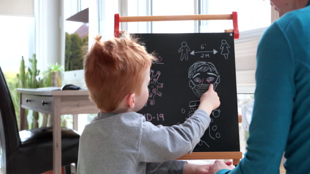 mother teaching redhead son about coronavirus and covid-19 - explaining stock videos & royalty-free footage