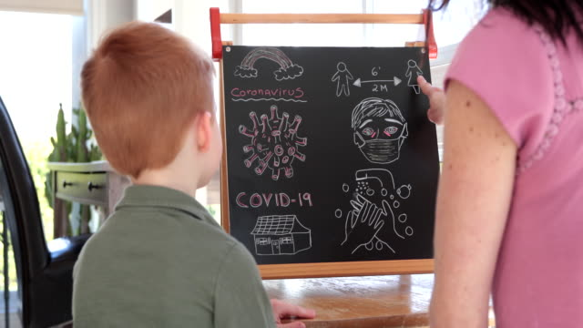 mother teaching redhead son about coronavirus and covid-19 - protective workwear stock videos & royalty-free footage