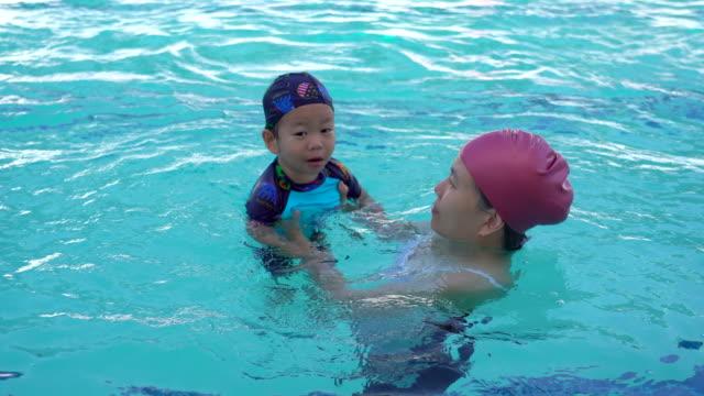 sohn mutter lehre wie zum schwimmen - schwimmflügel stock-videos und b-roll-filmmaterial