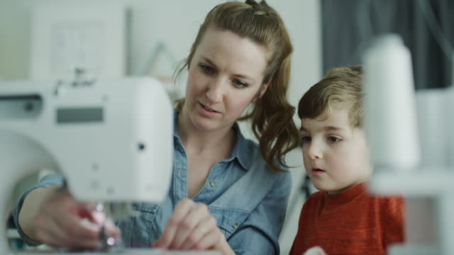 mother teaching son how to thread a sewing machine / lehi, utah, united states - cucire video stock e b–roll