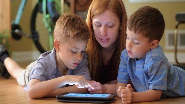 mother teaching sons using digital tablet. - the alphabet stock videos & royalty-free footage