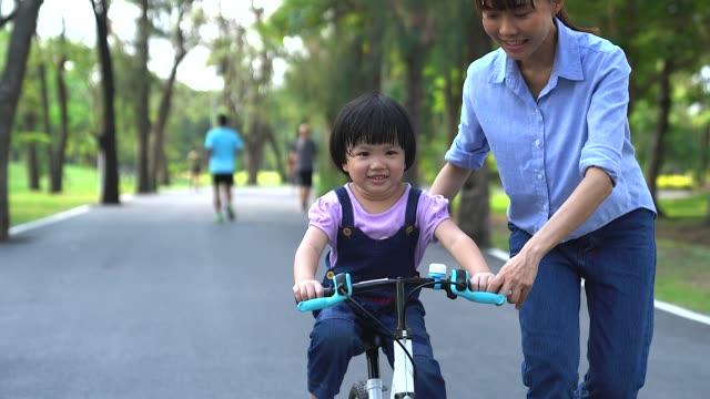 mutter unterrichtet einem kleinen mädchen auf dem fahrrad in einem sonnigen park. vorschulkinder lernen, sich auf dem fahrrad im öffentlichen park auszubalancieren. - teaching stock-videos und b-roll-filmmaterial