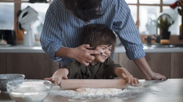 mother teases her son, having fun while making gingerbread cookies - biscuit stock videos & royalty-free footage