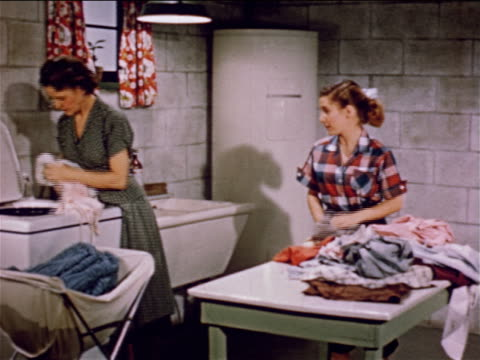 1955 mother + teen daughter talking in basement / woman handling clothing by washing machine