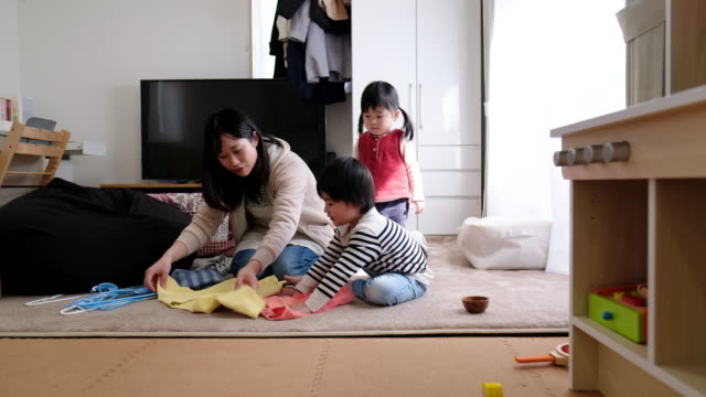 vídeos de stock e filmes b-roll de mother telling child how to fold laundry - arrumado