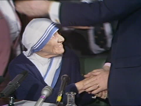 mother teresa in london:; b) england: london: int mother teresa sitting behind mikes as shakes hands with man tx:13.4.88/naf - itv news at five stock videos & royalty-free footage