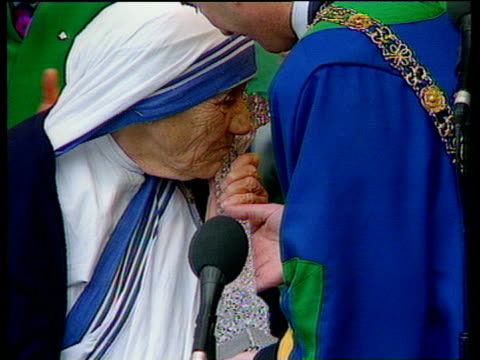 Mother Teresa kissing crystal model of Celtic Cross presented to her during ceremony giving her