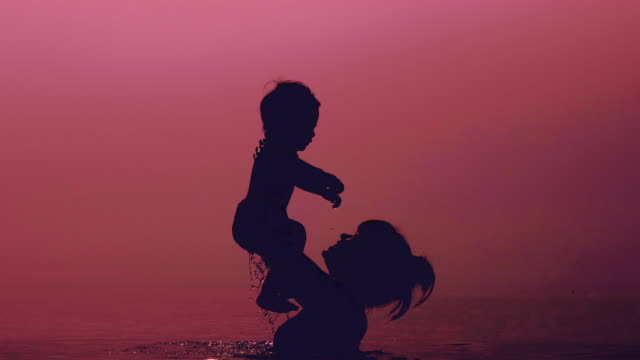 Mother throwing son in sea at sunset