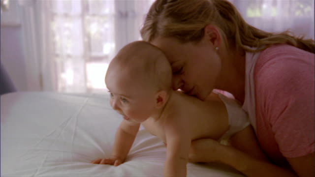 slo mo cu mother tickling and kissing baby girl on bed / los angeles, california, usa - nappy stock videos and b-roll footage