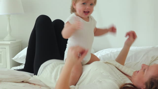 ms mother tickling baby girl (12-23 months) on bed / jersey city, new jersey, usa - tutina video stock e b–roll