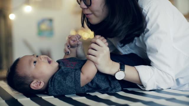 母はテーブルの上のくすぐり笑い赤ちゃん息子 - living room点の映像素材/bロール