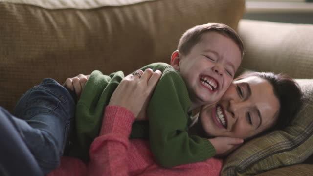 mother tickling son on sofa - kitzeln stock-videos und b-roll-filmmaterial
