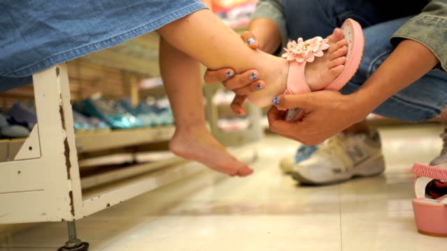mother try to fitting shoe for daughter  , slow motion - shoe stock videos & royalty-free footage