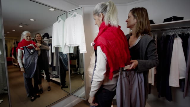 vídeos de stock, filmes e b-roll de ms mother trying outfits in fitting room, daughter assisting - cabine de loja