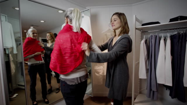 MS Mother trying outfits in fitting room, daughter assisting