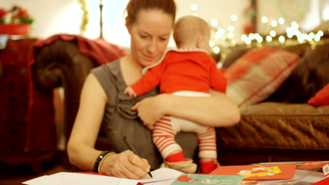 Mother trying to Write out Christmas cards with Baby