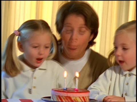 vídeos y material grabado en eventos de stock de mother + twin blonde girls blowing out birthday candles on cake together - familia con dos hijos