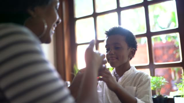 vídeos de stock, filmes e b-roll de mãe usando chocolate para brincar com o filho em casa - infância