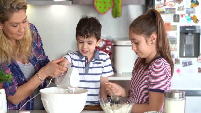 vidéos et rushes de mère 4k utilisant le masque protecteur faisant des petits gâteaux délicieux avec ses enfants isolement à la maison pour le virus - rester à la maison expression