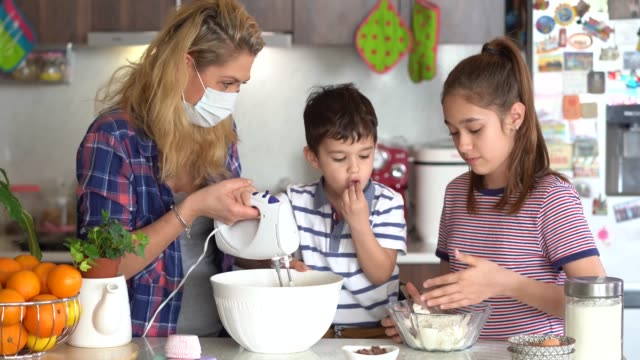 4k mother using protective mask  making delicious cupcakes with her children isolation at home for virus - isolamento video stock e b–roll