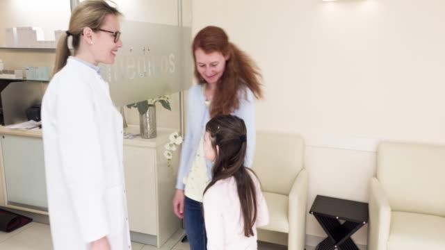 mother waiting for her daughter in doctors room - kvinnlig läkare bildbanksvideor och videomaterial från bakom kulisserna