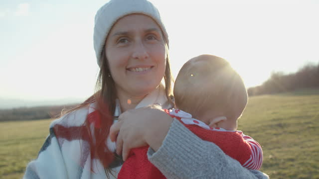 mother walking and playing with her newborn baby while being in the nature. spending time outdoors in fresh air during covid-19 pandemic. - hope concept stock videos & royalty-free footage