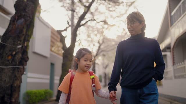 vidéos et rushes de mère marchant avec sa petite fille d'âge élémentaire à l'école - famille de deux générations