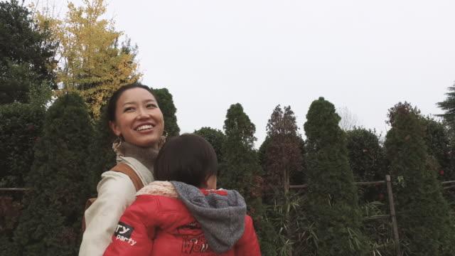 mother walking while hugging son - randoseru stock videos & royalty-free footage