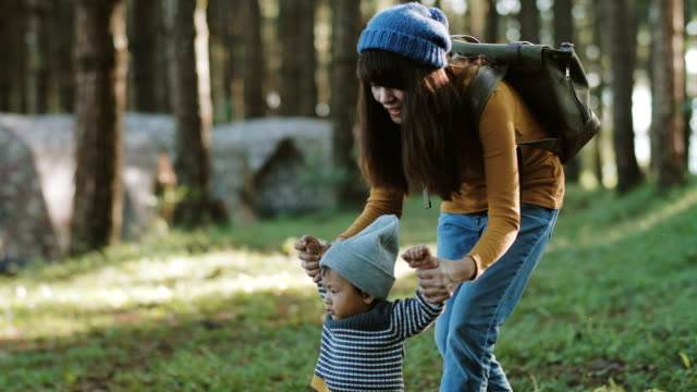 mother walking with baby holding hands in wood - primi passi video stock e b–roll