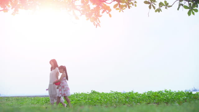 ws mother walking with her daughter under a tree. - focus on background stock videos & royalty-free footage