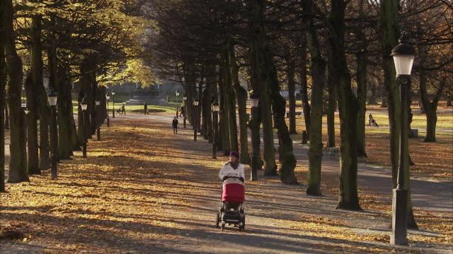 Mother walking with perambulator Sweden.