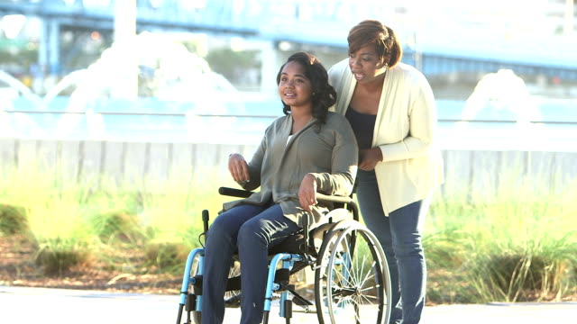 mother walking with teenage daughter in wheelchair - healthcare worker stock videos & royalty-free footage