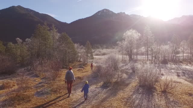 Mother walking with their kids between frozen trees