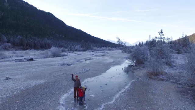 Mother walking with their kids in a frozen riverbed