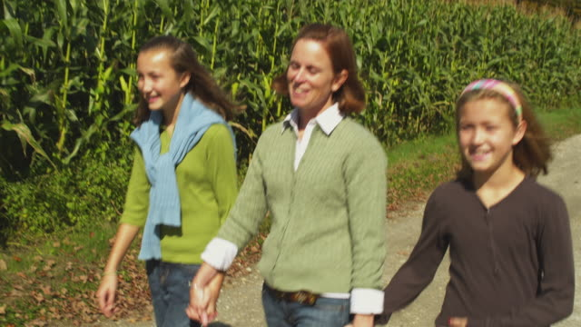 vidéos et rushes de ms pan mother walking with two daughters (11-12) along corn field, manchester, vermont, usa - manchester vermont