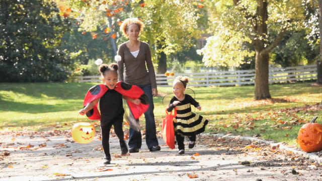 MS PAN Mother walking with two daughters (2-4) in Halloween costumes in park / Richmond, Virginia, USA