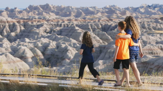 mother walks with son and daughter on scenic trail overlooking badlands national park. - badlands national park video stock e b–roll