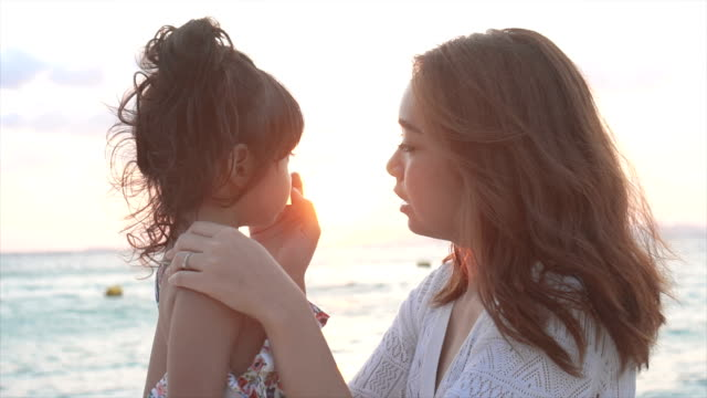mother was taking care of her daughter on the beach - back lit stock videos & royalty-free footage