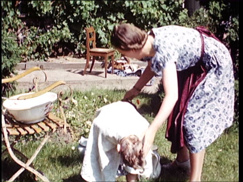 1937 ms mother washing daughter's hair in garden / horst, lower saxony, germany - 1937 stock-videos und b-roll-filmmaterial