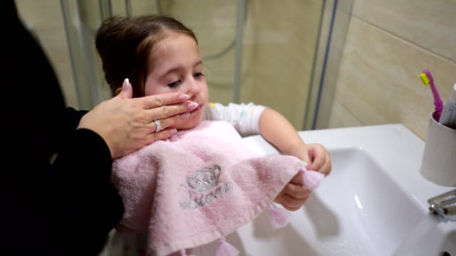 vidéos et rushes de mère lavant le visage de son enfant au-dessus de l'évier - salle de bains et toilettes