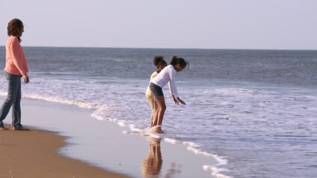 Mother watching daughters playing on beach in ocean waves